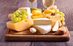 Many sorts of cheese with fruits. Over wooden board Royalty Free Stock Images