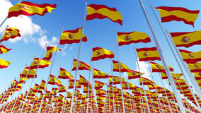 Many Spain Flags on flagpoles against blue sky. Royalty Free Stock Photos