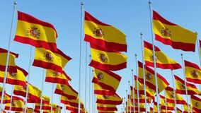 Many Spain flags in rows waving against clear blue sky Stock Photo