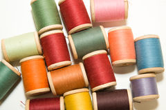 Many spools of thread of different colors on a white Stock Images