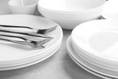 Many stacked plates with cutlery. Closeup stock photo