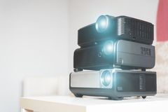 Many stacked projectors. Many stacked projectors on a table on a sofa background stock image