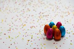 Many standing colored chocolate easter eggs on white background and colorful confetti royalty free stock photography