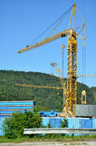 Many standing yellow tower cranes, forested hill and blue sky in background Royalty Free Stock Photos