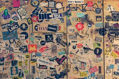 Many stickers of old logos on a wall of building. Royalty Free Stock Photos