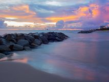 Many stones that are stacked in the sea and on a colorful sky background, sunset stock photo