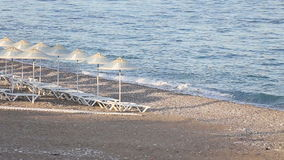 Many straw beach umbrellas at the seashore in stock video footage
