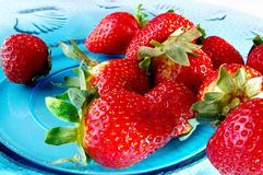 Many strawberries. On blue glass plate Royalty Free Stock Photography