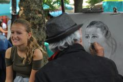 Paris,France - August 27,2017: Artist is drawing portrait for a girl on the street stock images