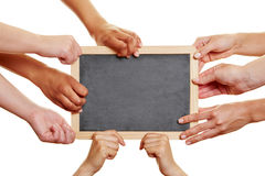 Many students holding empty blackboard. In their hands stock photos