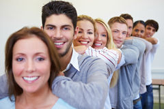 Many students in a row. Many happy smiling students leaning on shoulders in a row Stock Image
