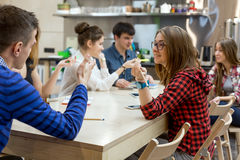 Many Students sitting at Wood Table of Campus and talking. Large Group of Students male and female relaxing at Wood Table of Campus Chat Room talking gesturing Royalty Free Stock Images