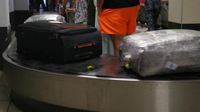 Many suitcases are riding around the luggage belt at the airport, people are watching their things. 3840x2160, 4K stock video footage