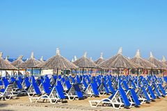 Many sun loungers. Comfortable sun loungers on sea beach at resort stock photo