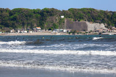 Many surfers catch wave on low tide shore in Yuigahama beach. The Sagami Bay is famous for wind surfing. Kamakura, Japan Royalty Free Stock Photography