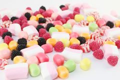 Many sweet candies and marshmallows on white surface. Closeup Royalty Free Stock Images