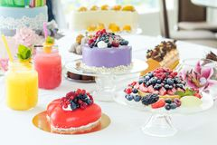 Many sweet pastries on white table with fresh summer berries. Fe. Stive table settings. Light background. Shallow depth of field Royalty Free Stock Photo