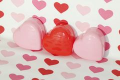 Many Sweetheart Valentine Hearts. Three red and pink sweetheart valentine hearts, with a pink, mauve and red background Stock Photo
