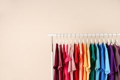 Many t-shirts hanging in order. Of rainbow colors on light background Royalty Free Stock Image