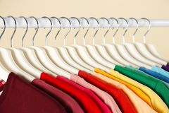 Many t-shirts hanging in order of rainbow colors,. Closeup royalty free stock photography