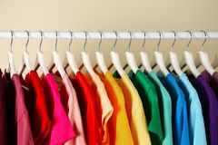 Many t-shirts hanging in order of rainbow colors. Closeup stock photography