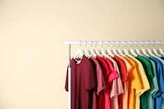 Many t-shirts hanging in order of rainbow colors. On light background stock photo