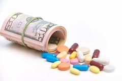 Many tablets or pills lie near rolled up dollars, symbolize paid expensive medicine and corruption, isolated over white background. Medicine, health and Royalty Free Stock Photography