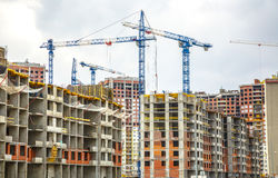 Many tall buildings and cranes Stock Photos