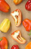 Many tasty sweet peppers on kitchen desk Stock Photos