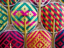Many Thai style colorful wooden handmade fan arrange on the wall.  Stock Photos