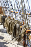 Many thick ropes bend together on a ship. Many brownish thick ropes bend together in a sailing ship Stock Image