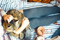 Woman and cat. Many threads. Woman holds cat on bed. Flat lay stock photography