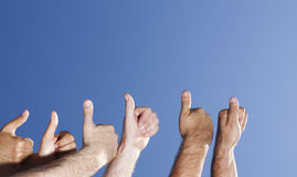 Many thumbs over blue sky Stock Photography