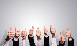 Many thumbs up on grey background Stock Image