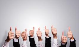 Many thumbs up on grey background Stock Image