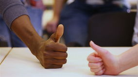 Many thumbs up on a table Stock Images