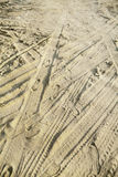 Many tire tracks and footprints in different directions on the beach sand Royalty Free Stock Photo