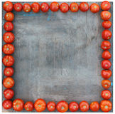 Many tomatoes lined up around square wooden board as a frame. Background image Stock Images