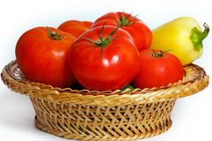 Many tomatoes and pepper in a basket Stock Images