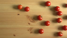 Many tomatoes roll on wooden surface. Slow Motion. Top view. stock footage