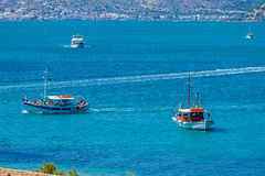 Many touristic ships floating in sea bay near Spinalonga fortres Royalty Free Stock Photography