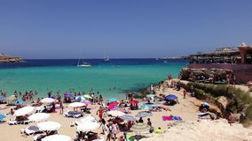 Many tourists at Cala Conta beach in Ibiza stock video