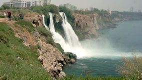Many tourists came to see and take pictures of the beautiful waterfall on the cliff.  stock footage