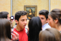 Many tourists in front of the Mona Lisa (Monna Lisa or La Gioconda in Italian and La Joconde in French) painting at the Louvre Mus Stock Images