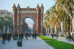 Many tourists near the Arc de Triomphe, Barcelona, Spain. BARCELONA, SPAIN - DECEMBER 26, 2015: Many tourists near the Arc de Triomphe in sunny winter day Royalty Free Stock Photography