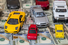Many toy cars on dollar. Background Royalty Free Stock Photos