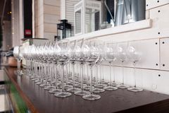 Many transparent crystal wine glasses stand in row on the brown wooden shelves of the rack. Side view. Concept of tasting, banquet stock photography