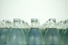 Many of transparent glass bottle into row. The production of glass bottles and beverage stock images
