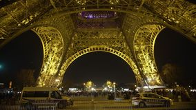 Many travellers walking around Eiffel Tower in Paris at night, police on duty. Stock footage stock footage