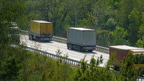 Many trucks and cars driving on the highway among the trees. Transportation is one of the main engines of trade stock video footage